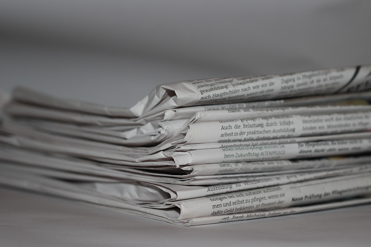 A pile of news papers on a bench