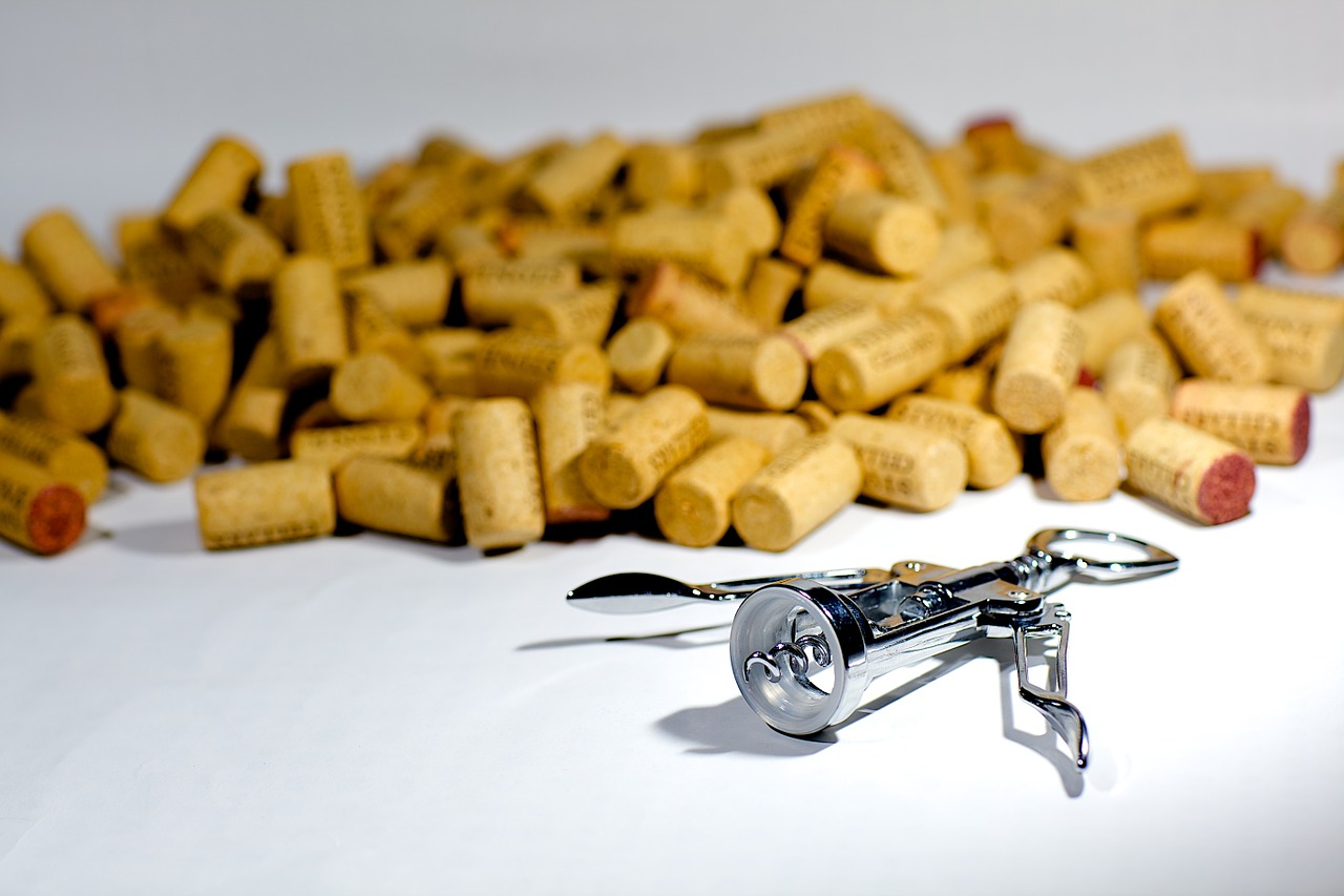 pile of Italian wine corks and a silver corkscrew