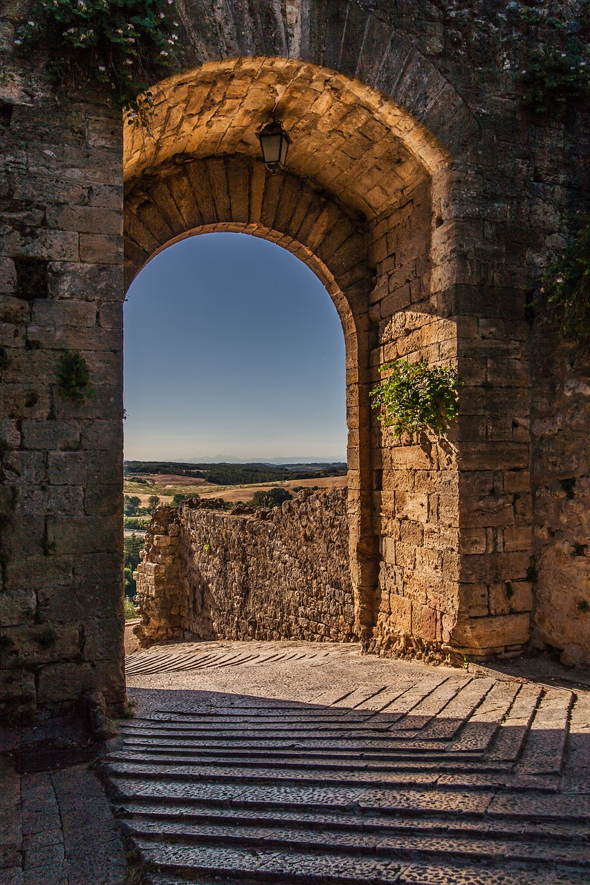 A stone-clad archway leading out on to a stone path in Monteriggioni
