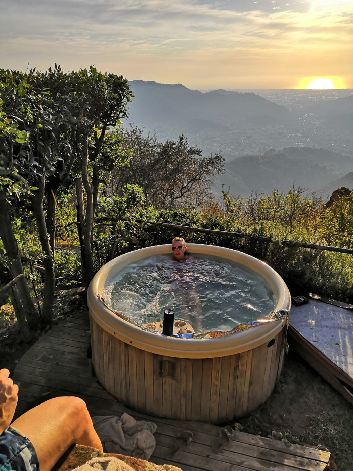 A man in a hot tub overlooking Tuscany at sunset