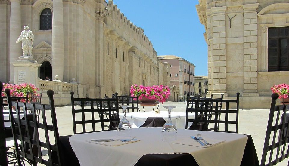 A white dining table with pink flowers overlooking the Piazza Duomo in Syracuse, Sicily, Italy