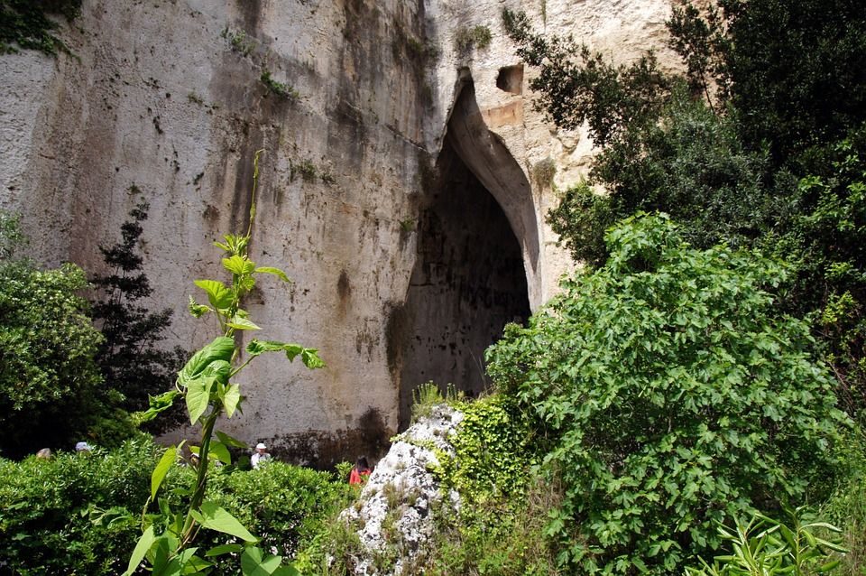 The Ear of Dionysus behind some bushes in Syracuse, Sicily, Italy