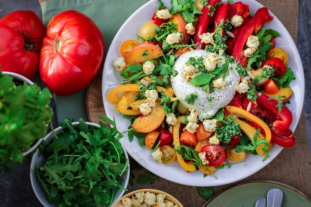 Burrata cheese ball on top of salad with coloured peppers