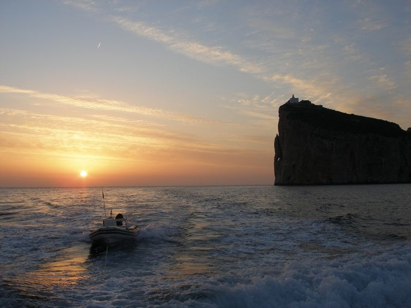Small boat drives from Capo Cacci caves at sunset.