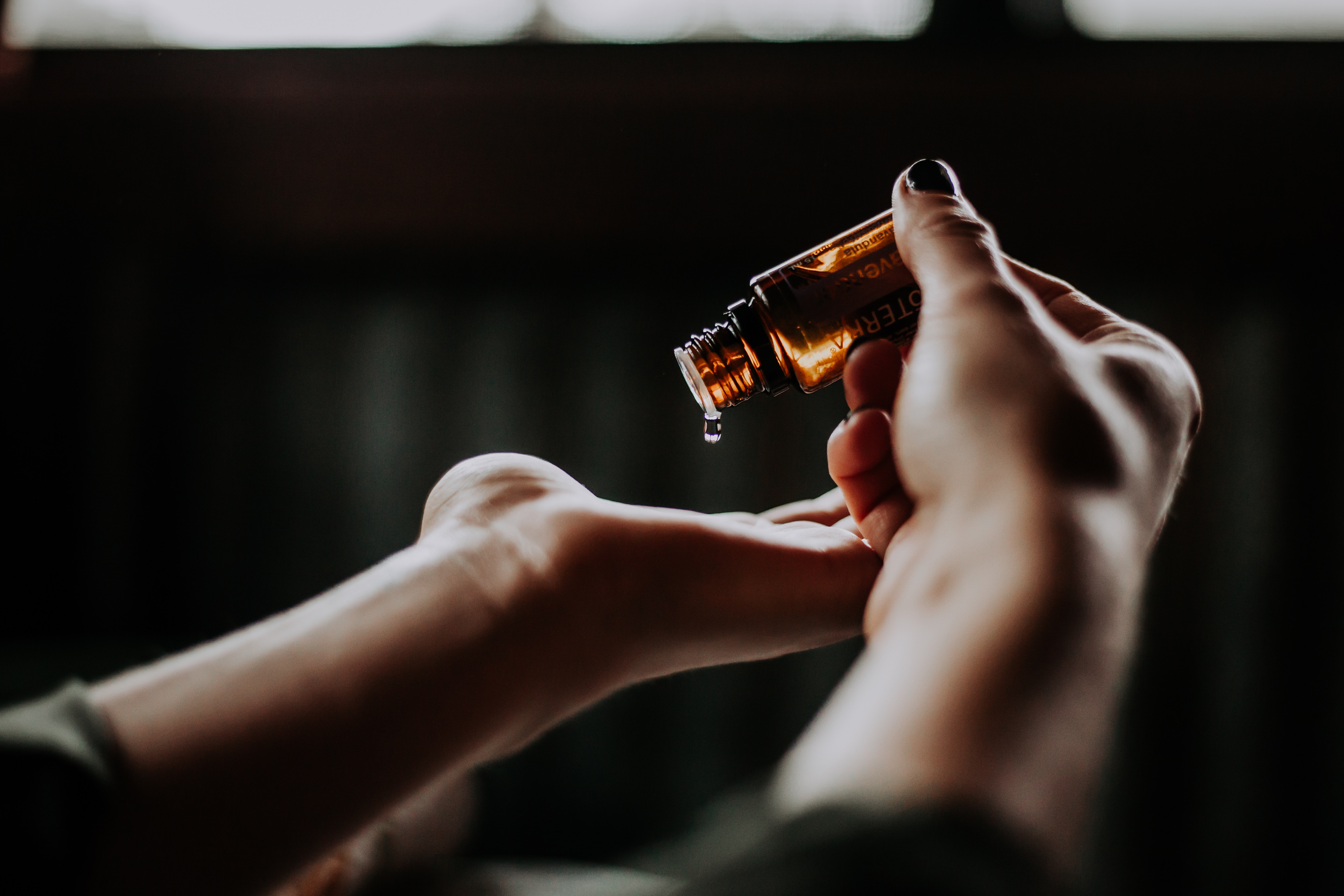A girl pouring oils onto her palm.
