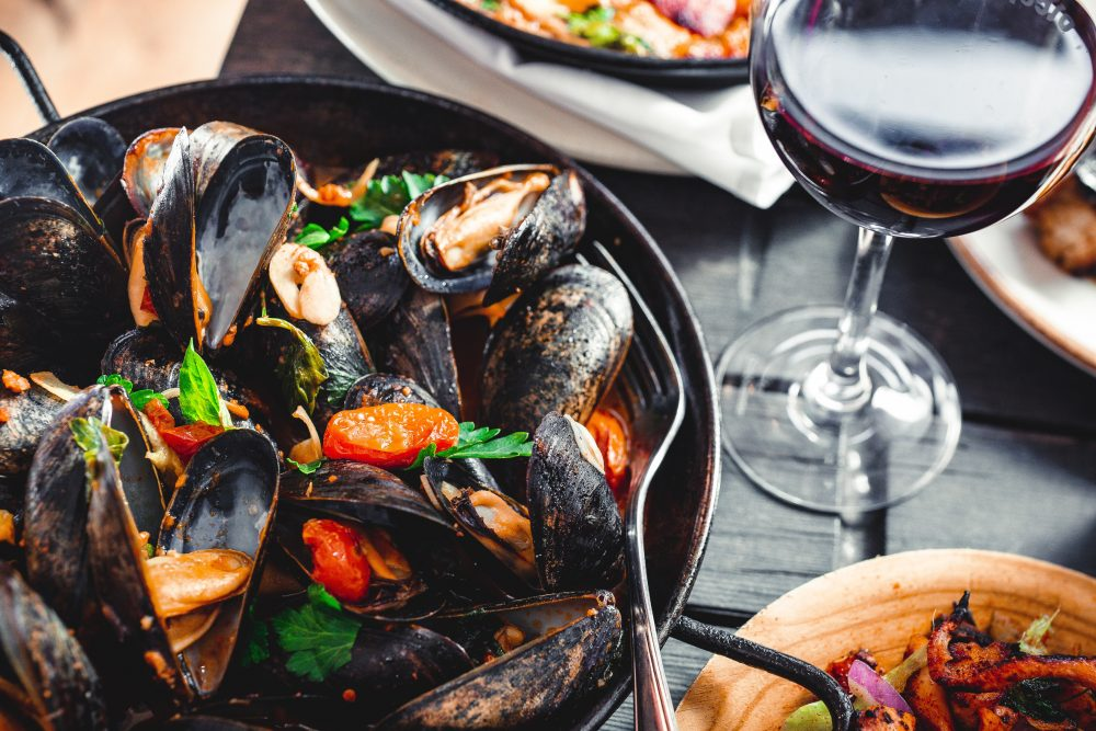 Bowl of mussels and glass of red wine.