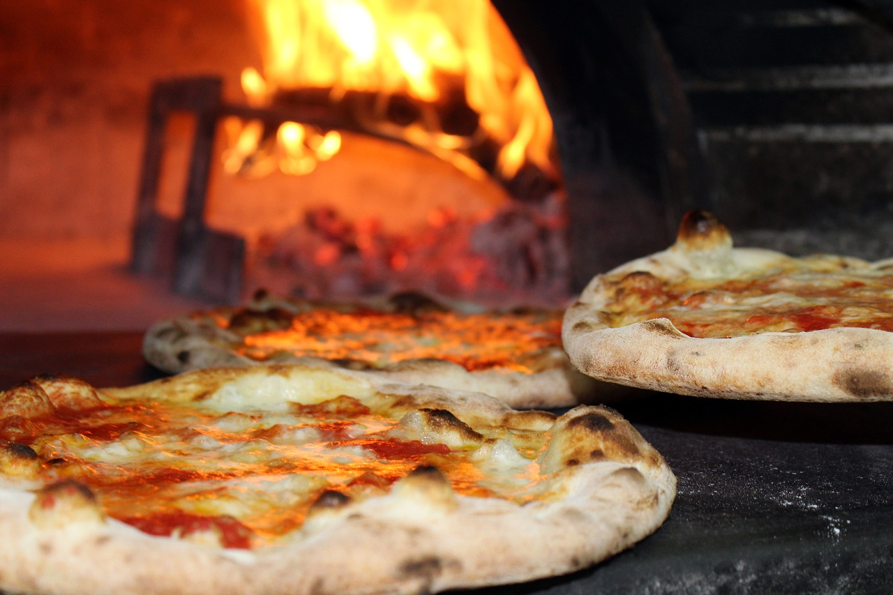 Two pizzas in front of a blazing pizza oven.
