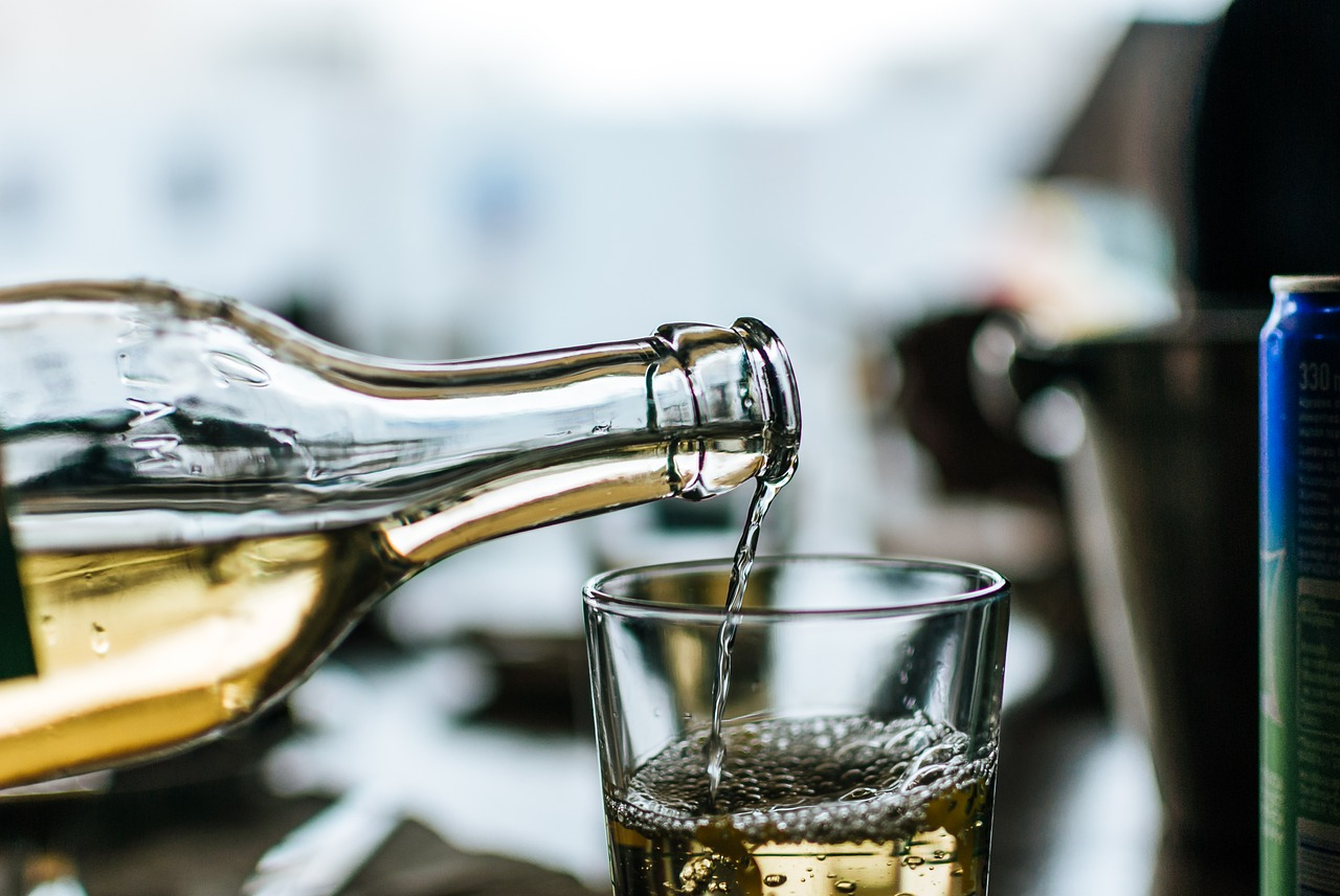 Bottle of white wine being poured into glass.