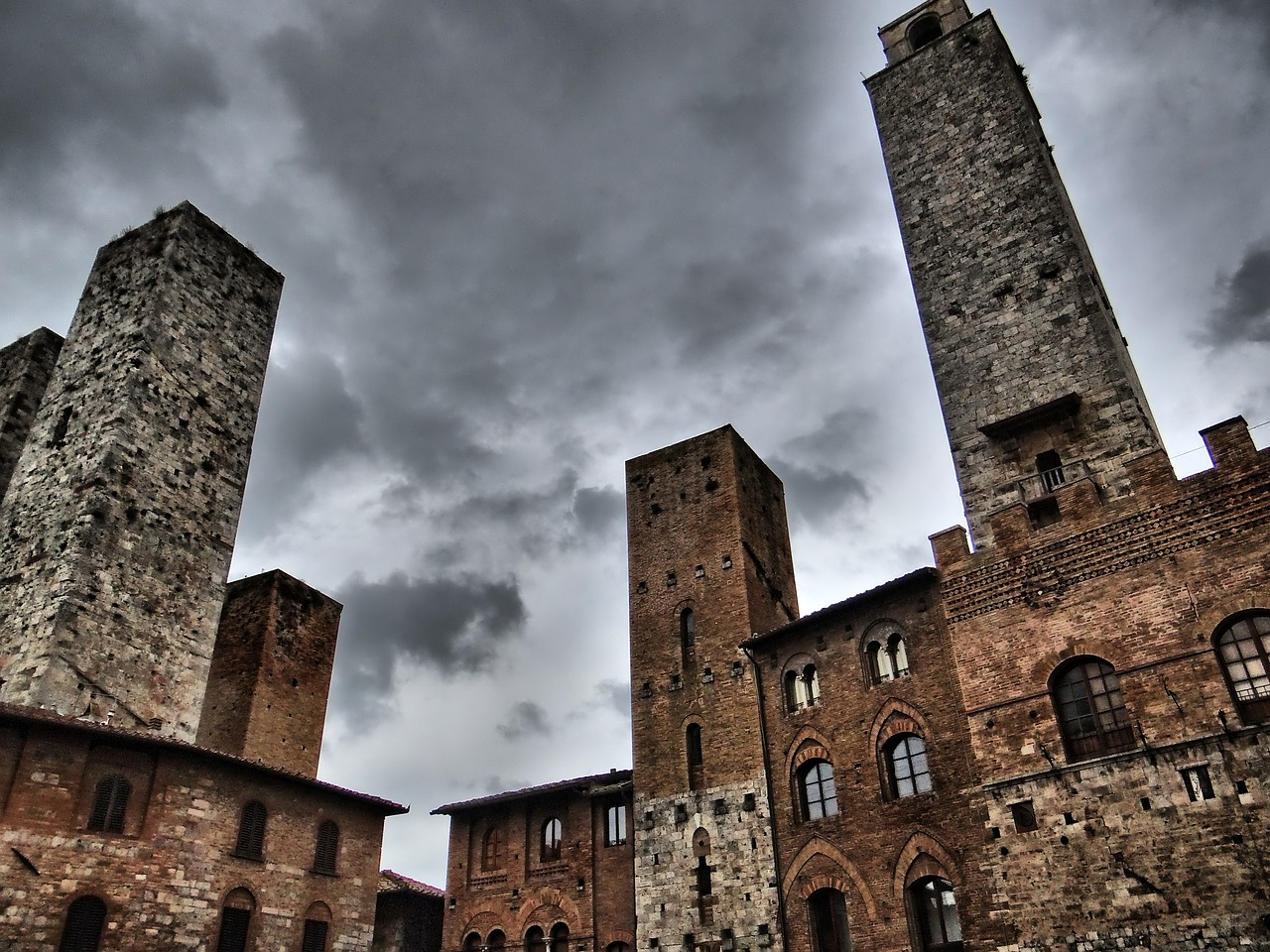 Imposing looking tower in San Gimignano with dark clouds in background.