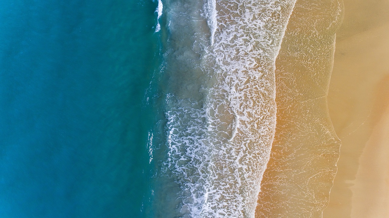 Ariel view of blue sea and golden sand.