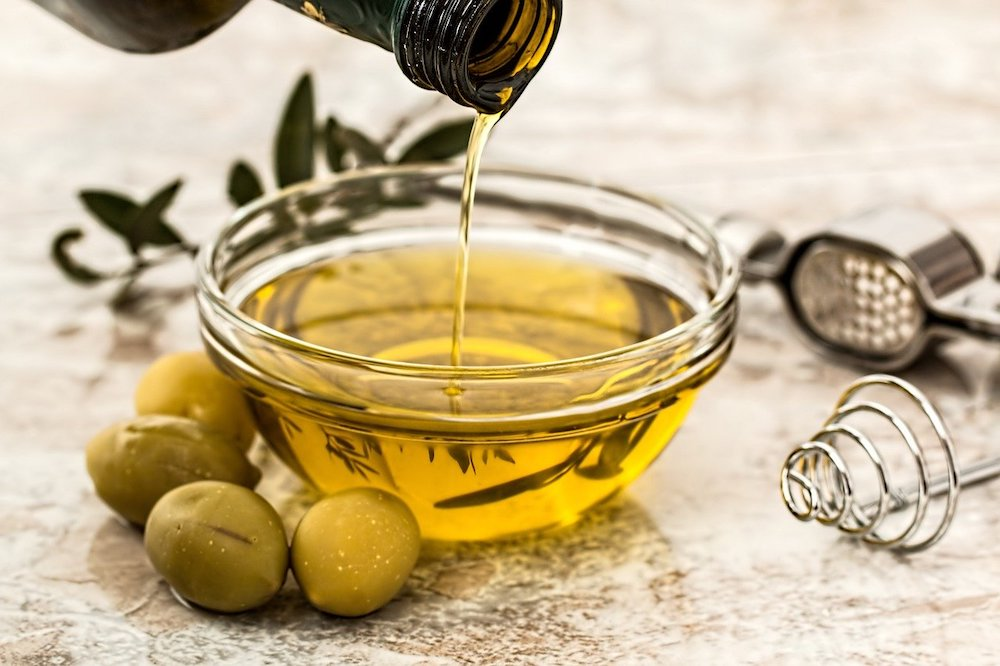 Glass bowl of olive oil.