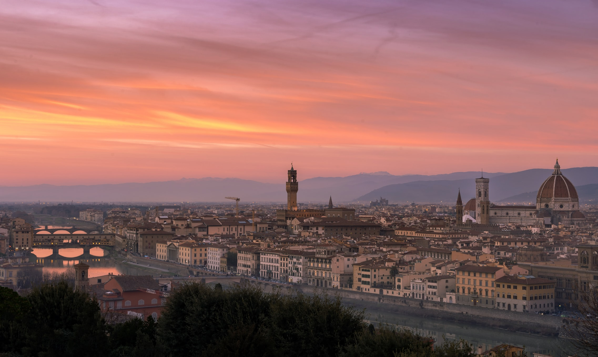 Piazzale Michelangelo panoramic view of Florence with bright orange and pink sunset sky