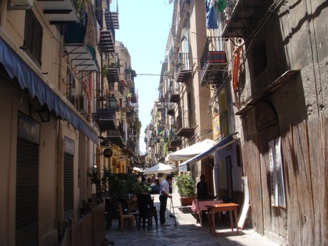 A narrow alley with market stalls, balconies and people in Palermo, Sicily