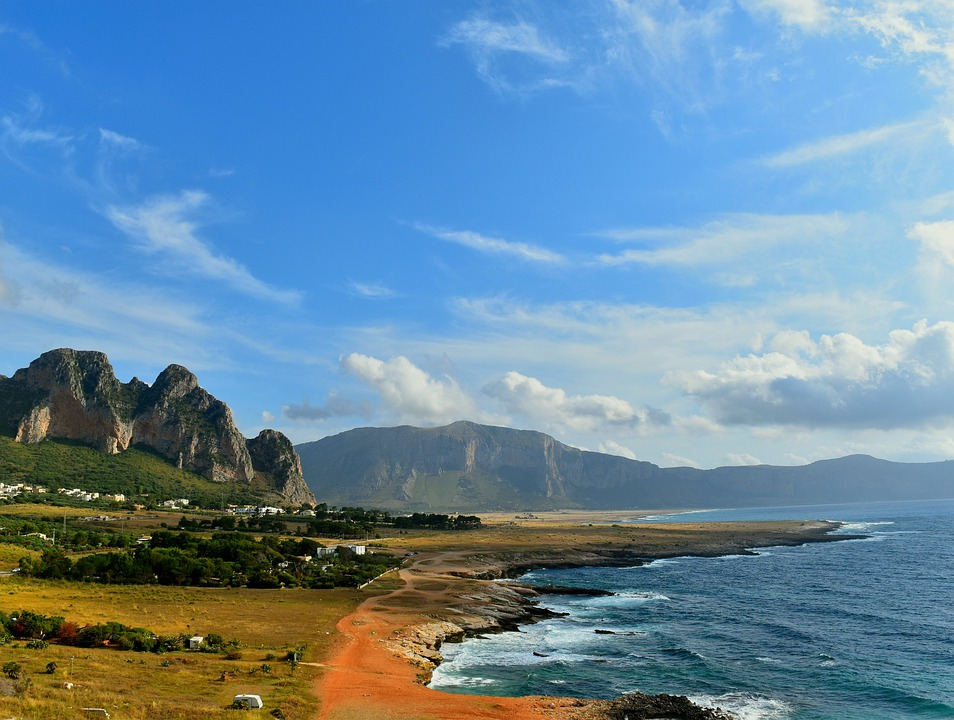 The coast of Sicily on a sunny day, with mountains and grass plains